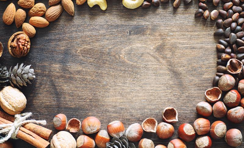 Different nuts on a wooden table. Cedar, cashew, hazelnut, walnu. Ts and a spoon on the table. Many nuts are inshell and chistchenyh on a wooden backgroundr stock photo