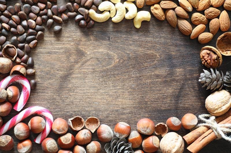 Different nuts on a wooden table. Cedar, cashew, hazelnut, walnu. Ts and a spoon on the table. Many nuts are inshell and chistchenyh on a wooden backgroundr stock images