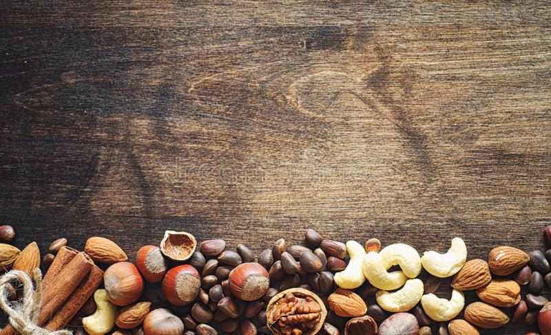 Different nuts on a wooden table. Cedar, cashew, hazelnut, walnu. Ts and a spoon on the table. Many nuts are inshell and chistchenyh on a wooden backgroundr royalty free stock photo