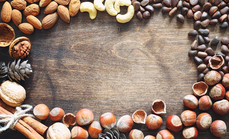 Different nuts on a wooden table. Cedar, cashew, hazelnut, walnu. Ts and a spoon on the table. Many nuts are inshell and chistchenyh on a wooden backgroundr royalty free stock images