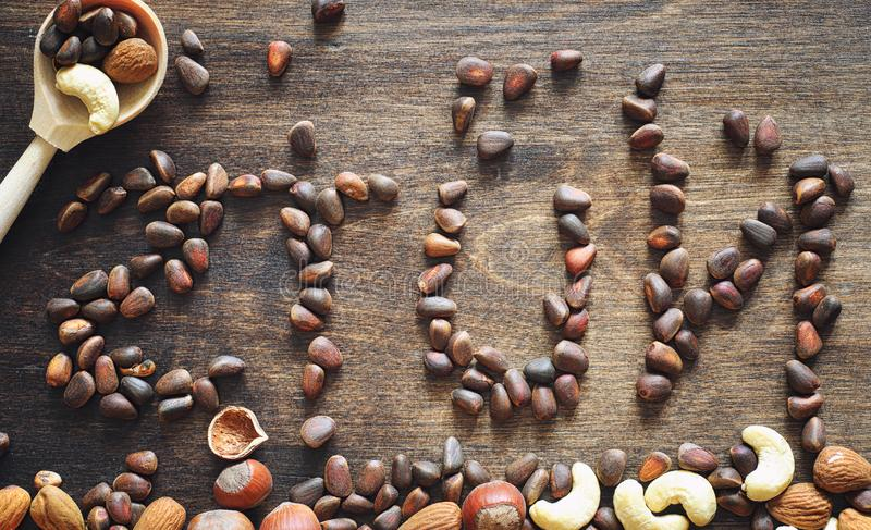 Different nuts on a wooden table. Cedar, cashew, hazelnut, walnu. Ts and a spoon on the table. Many nuts are inshell and chistchenyh on a wooden backgroundr royalty free stock photos