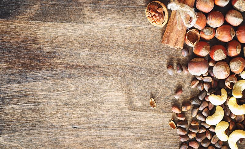 Different nuts on a wooden table. Cedar, cashew, hazelnut, walnu. Ts and a spoon on the table. Many nuts are inshell and chistchenyh on a wooden backgroundr stock photography