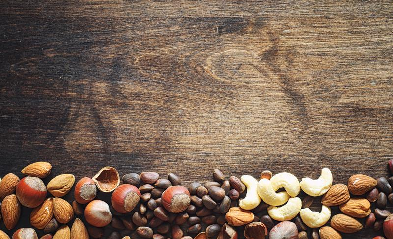 Different nuts on a wooden table. Cedar, cashew, hazelnut, walnu. Ts and a spoon on the table. Many nuts are inshell and chistchenyh on a wooden backgroundr stock image