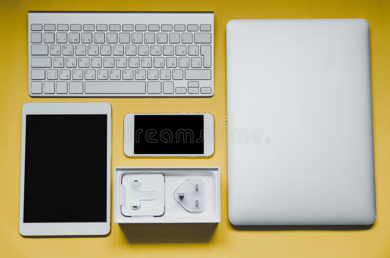 Different office devices on yellow background, top view stock image