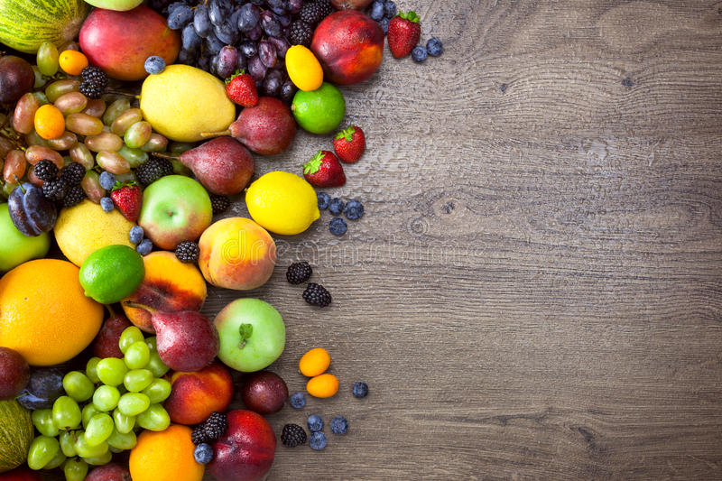 Different Organic Fruits with water drops on wooden table back. Ground - Healthy Eating royalty free stock images
