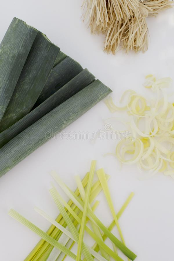 Different parts of a leek in a white background. Leek top, leek roots, and leek cut straight and round way stock images