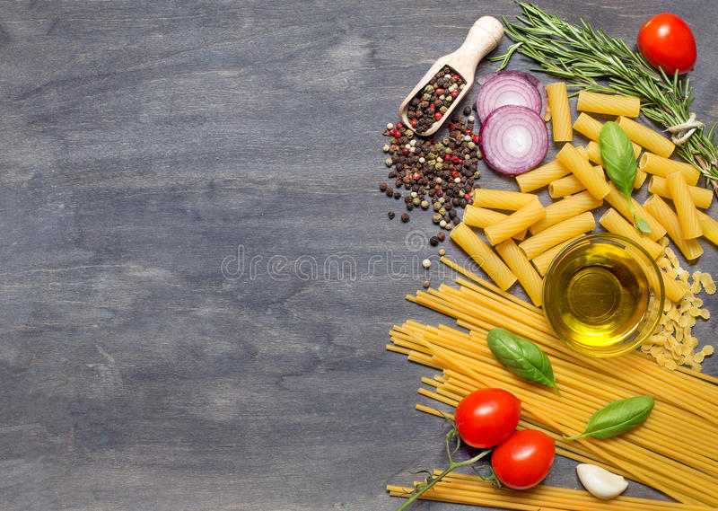 Different pasta, condiment, olive oil and tomatoes on dark woode stock images