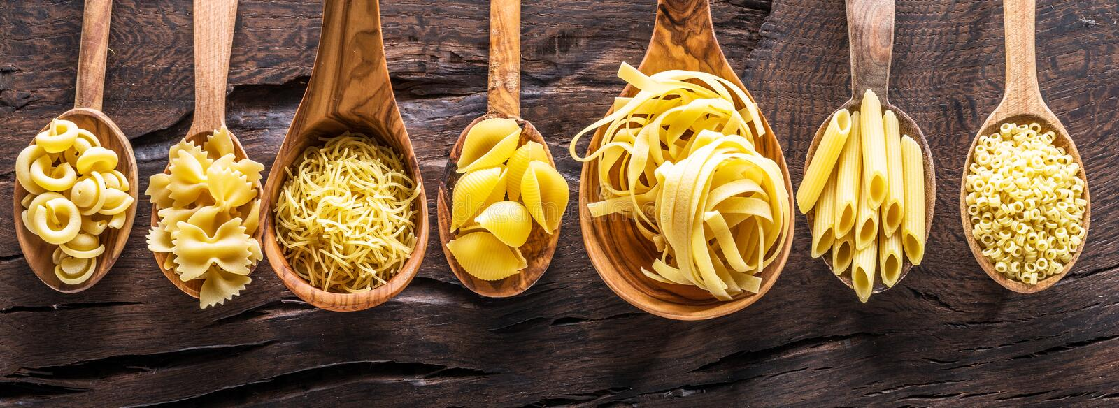 Different pasta types in wooden spoons on the table. Top view. royalty free stock photography