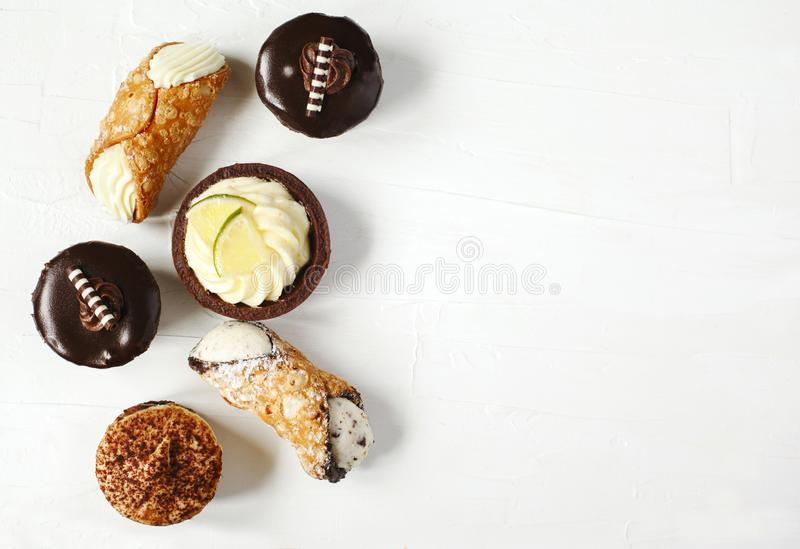 Different pastries on white background: cannoli with ricotta, tartlets filled with citrus cream, fudge cake, tiramisu cake. Top view, copy space royalty free stock photo