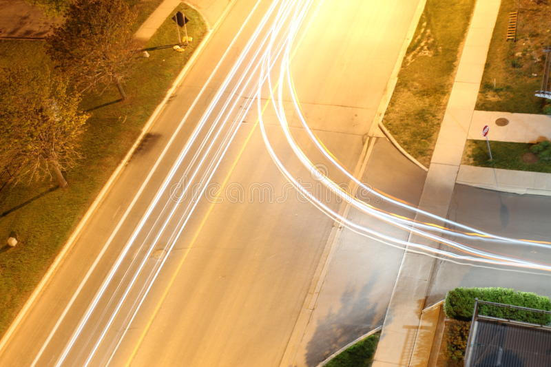 Different Paths. This photo is a long-exposure photograph of a small intersection that shows the light trails of two different vehicles coming from the same side stock image