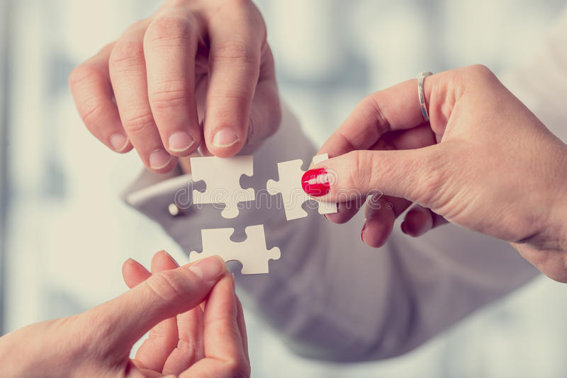 Different people matching three puzzle pieces stock photography