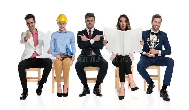 Different people sitting on chairs and each doing something else royalty free stock image