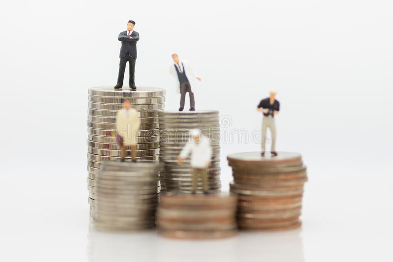 Different people standing on stack coins, using as salaries are different from many occupations concept stock photo