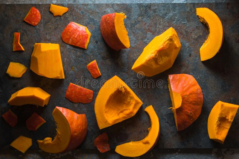 Different pieces of a pumpkin on a blue stone. Horizontal royalty free stock photography