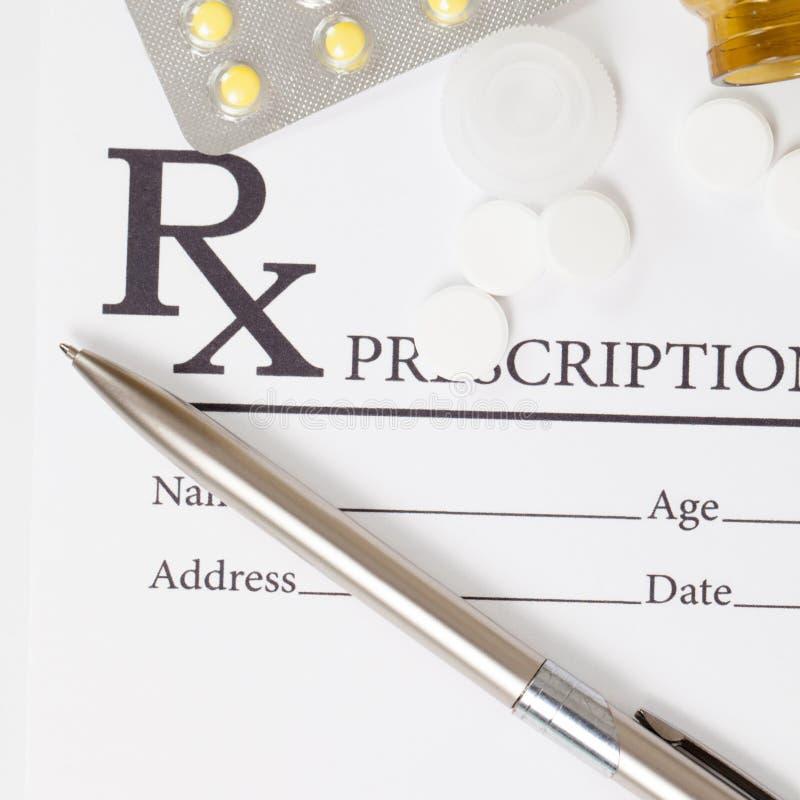 Different pills and silver color pen over medical prescription form - close up studio shot stock image