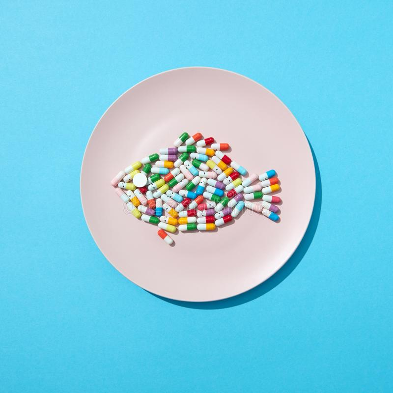 Fish from colorful pills and tablets on a white plate on a blue background with copy space. Colorful food supplement royalty free stock photography