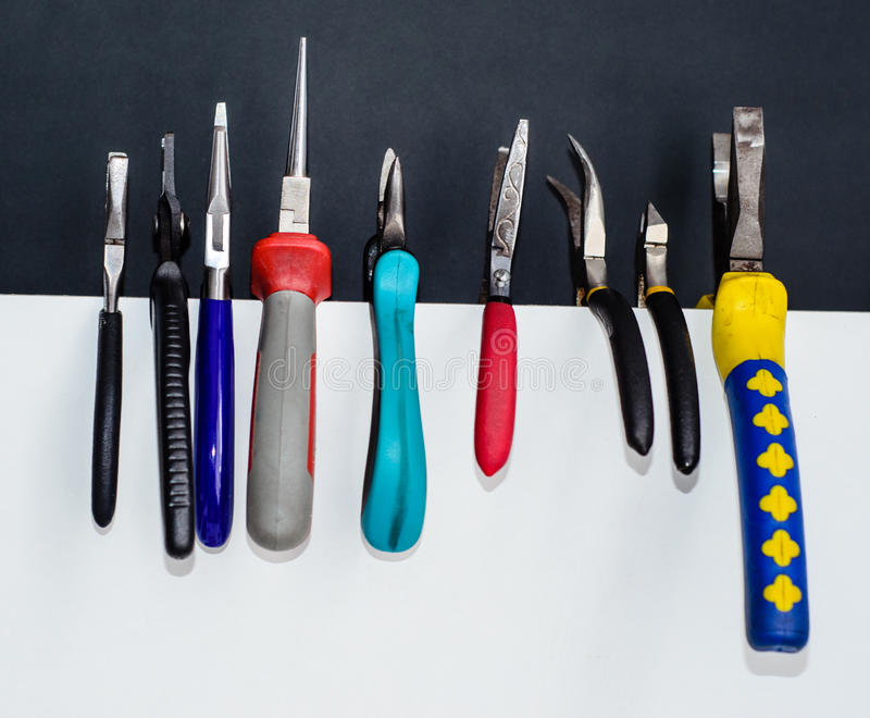 Different pliers on a white chipboard royalty free stock photography