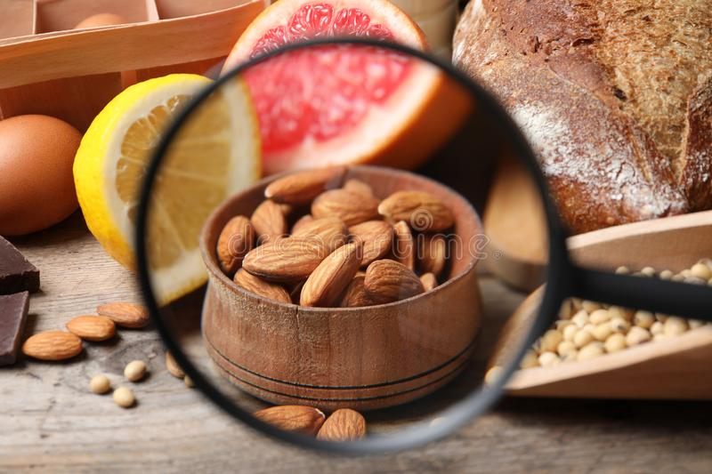 Different products with magnifier on almonds, closeup. Food allergy concept. Different products with magnifier focused on almonds, closeup. Food allergy concept stock images