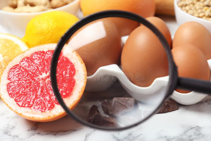 Different products with magnifier ed on eggs and grapefruit, closeup. Food allergy concept. Different products with magnifier focused on eggs and grapefruit royalty free stock images