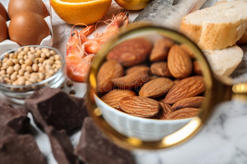 Different products with magnifier focused on almonds. Food allergy concept. Different products with magnifier focused on almonds, closeup. Food allergy concept stock photography