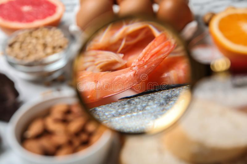 Different products with magnifier focused on  and fish, closeup. Food allergy concept. Different products with magnifier focused on shrimps and fish, closeup stock photography