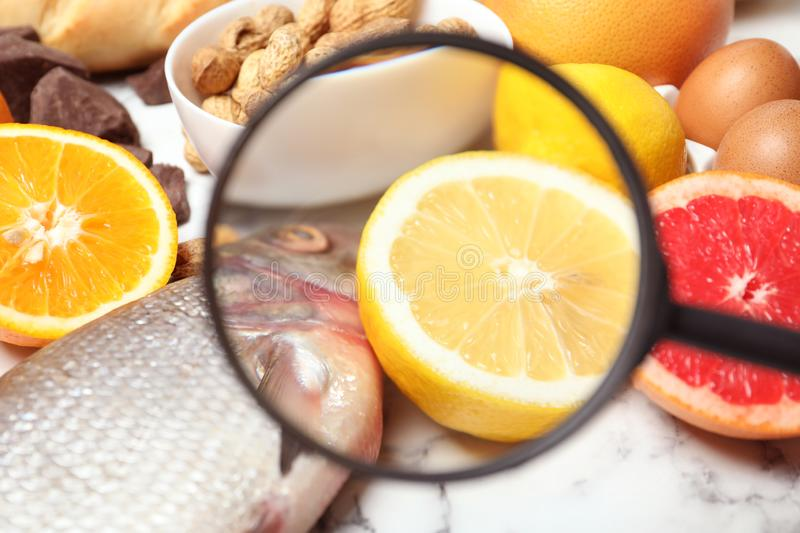 Different products with magnifier focused on fish and lemon. Food allergy concept. Different products with magnifier focused on fish and lemon, closeup. Food royalty free stock photos