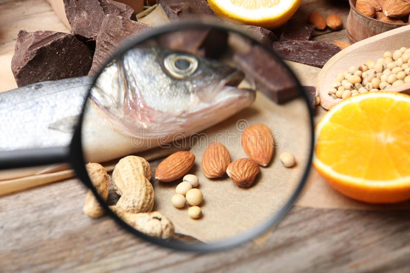 Different products with magnifier focused on fish and nuts. Food allergy concept. Different products with magnifier focused on fish and nuts, closeup. Food royalty free stock photography