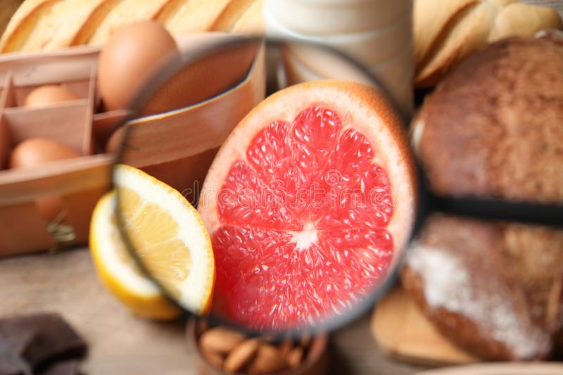 Different products with magnifier focused on grapefruit and lemon. Food allergy concept. Different products with magnifier focused on grapefruit and lemon royalty free stock images