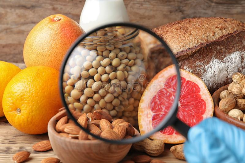 Different products with magnifier focused on jar of soy. Food allergy concept. Different products with magnifier focused on jar of soy, closeup. Food allergy royalty free stock photo
