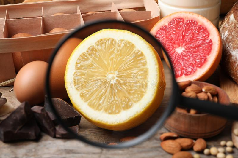Different products with magnifier focused on lemon. Food allergy concept. Different products with magnifier focused on lemon, closeup. Food allergy concept royalty free stock photo