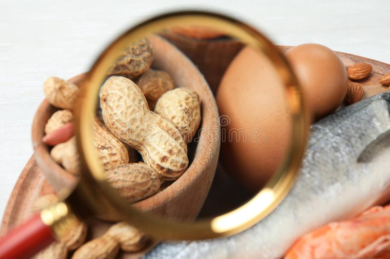 Different products with magnifier focused on peanuts and eggs. Food allergy concept. Different products with magnifier focused on peanuts and eggs, closeup. Food royalty free stock photos