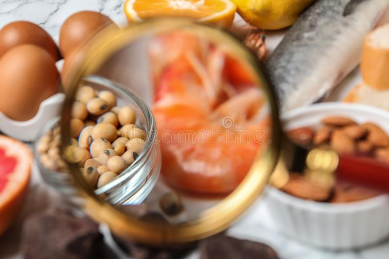 Different products with magnifier focused on shrimps and soy beans. Food allergy concept. Different products with magnifier focused on shrimps and soy beans stock images