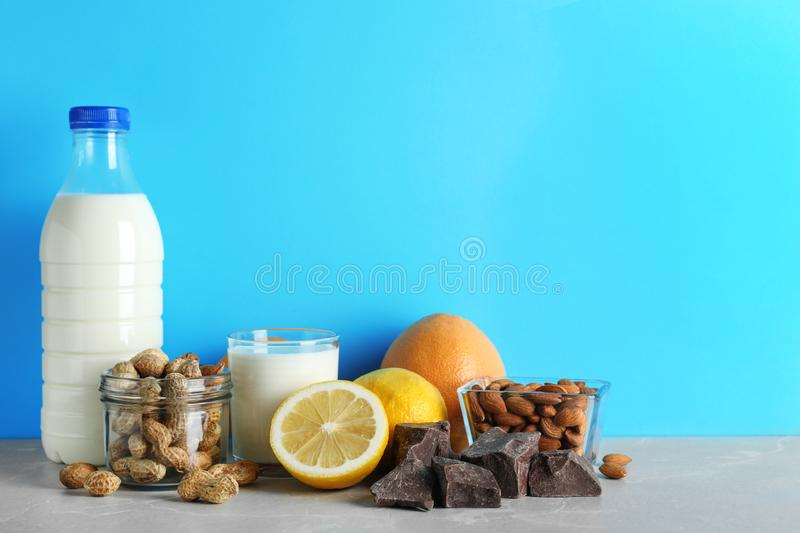 Different products on stone table against light blue background. Food allergy concept. Different products on stone table against light blue background, space for stock photos