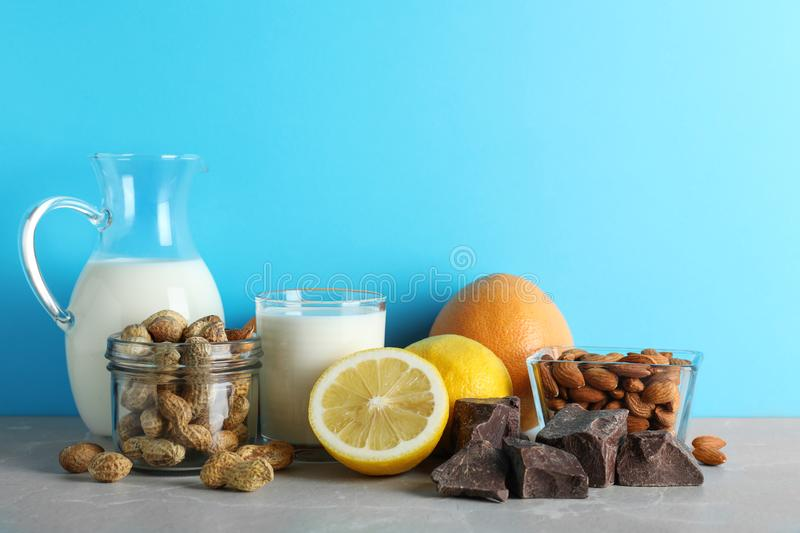 Different products on stone table against light blue background. Food allergy concept. Different products on stone table against light blue background, space for royalty free stock photo