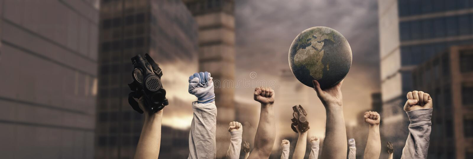 Different raising up left fists protest against climate change in front of city and sunset in depth of field royalty free stock images