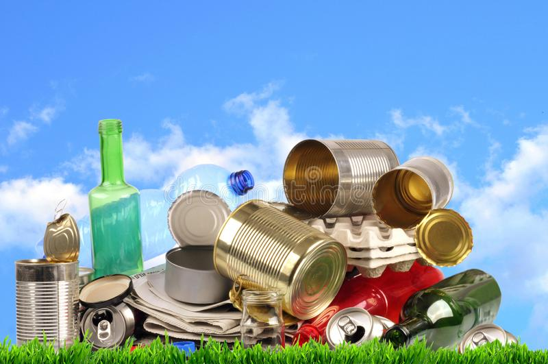 Different recyclable materials stacked on grass royalty free stock image