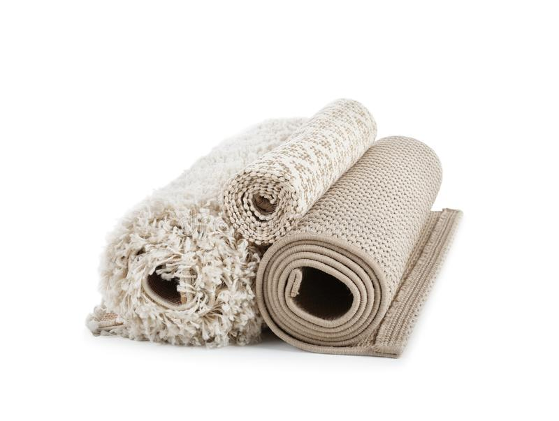 Different rolled carpets on white background royalty free stock image