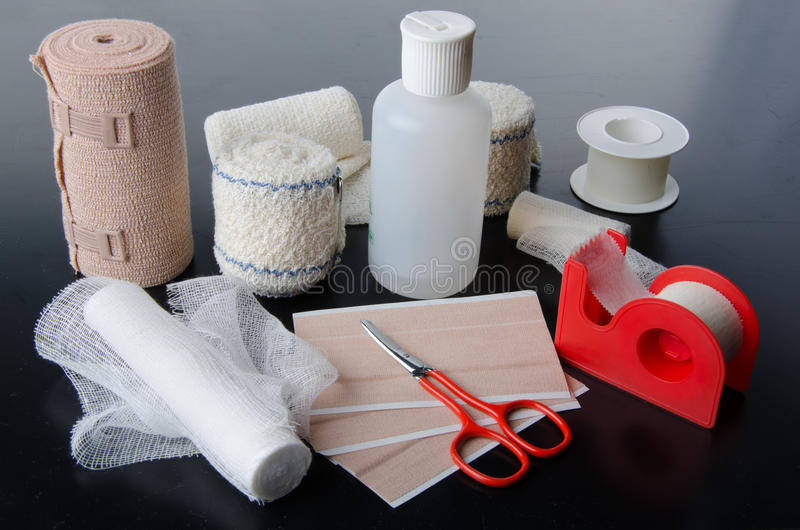 Different rolls of medical bandages and care equipment. On a black background stock photo