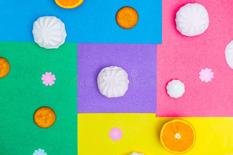 Different round sweets - cookies, meringue, marshmallow on multicolor bright background. Sweet candy minimalism geometry concept. stock photos
