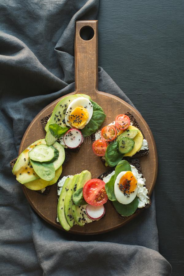 Different sandwiches with vegetables, eggs, avocado, tomato, rye bread on black chalkboard background. Top vew. Appetizer for part. Different sandwiches with stock photography