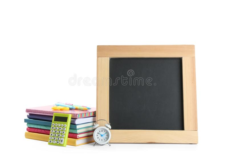 Different school and small blank chalkboard on white background. Space for text. Different school stationery and small blank chalkboard on white background stock photography