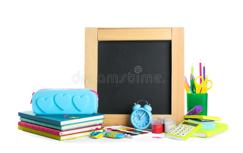 Different school stationery and blank chalkboard on white background. Space for text. Different school stationery and small blank chalkboard on white background royalty free stock photos