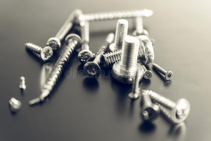 Different screws and bolts on reflective surface stock photography