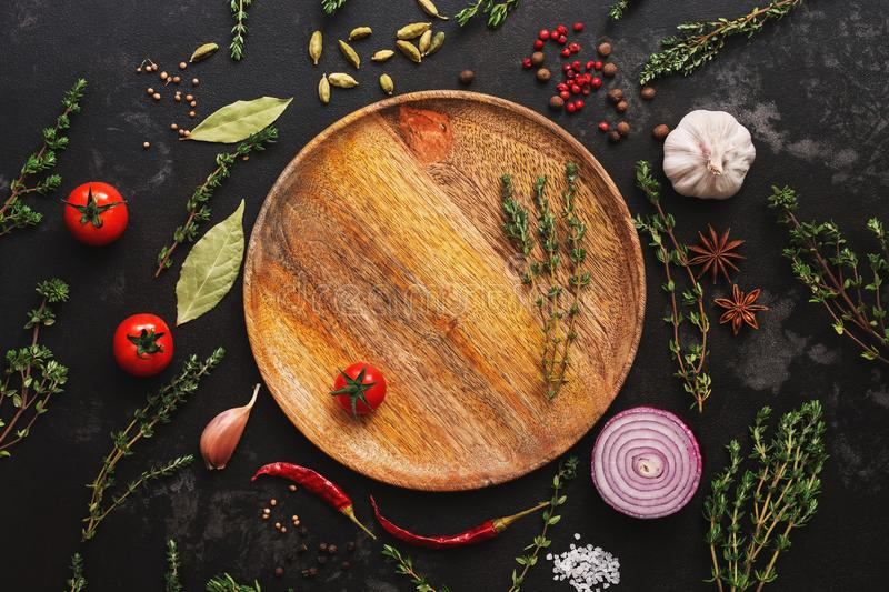 Different seasoning for cooking on a dark background. Empty wooden plate, spices, herbs, vegetables. Top view, flat lay stock photography