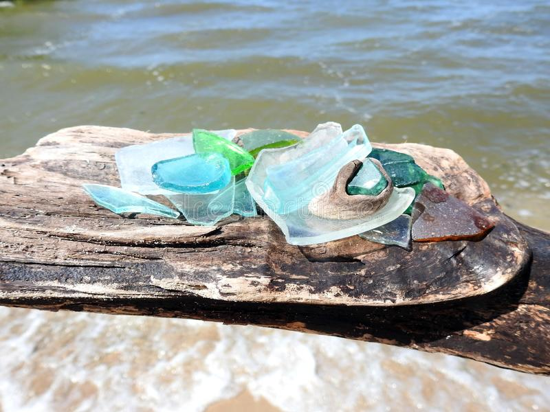 Different shape and colors glass pieces on wood near water, Lithuania stock photography