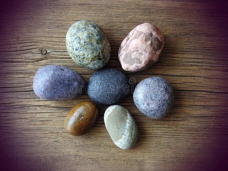 Different shape and colors stones on wooden surface royalty free stock photography