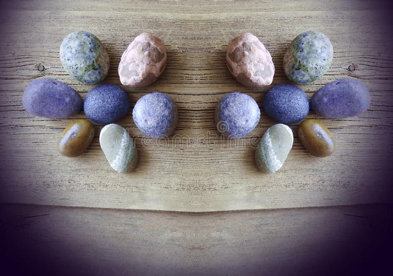 Different shape and colors stones on wooden surface stock image
