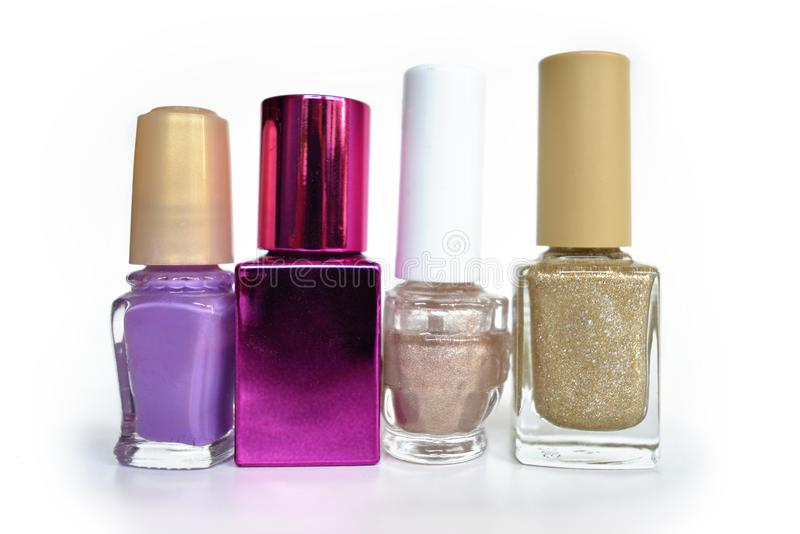 Different shaped bottles with purple, pink and shimmering golden color nail polish on white background royalty free stock photo