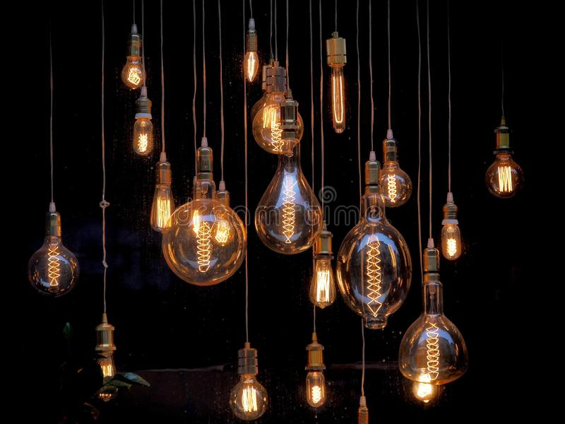 Different shaped vintage light bulbs on black background stock photo