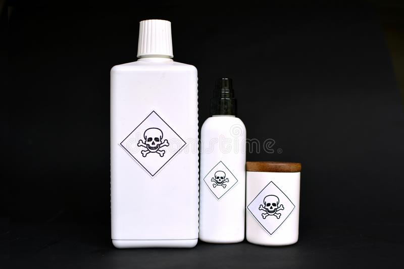Different shaped white containers with poison labels on black background stock photos
